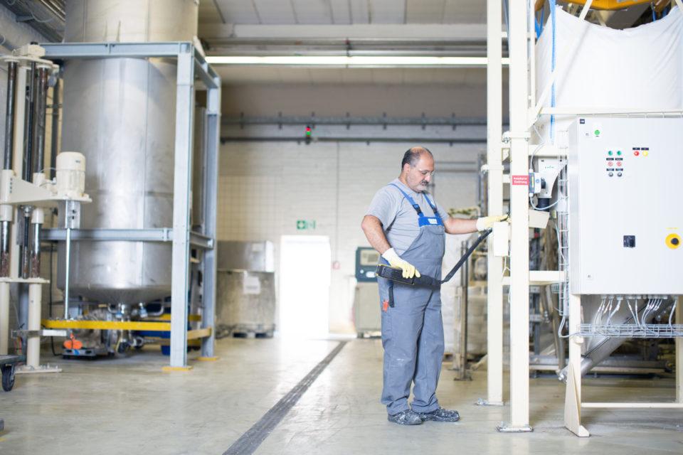 Mitarbeiter steht an Maschine in Produktionshalle