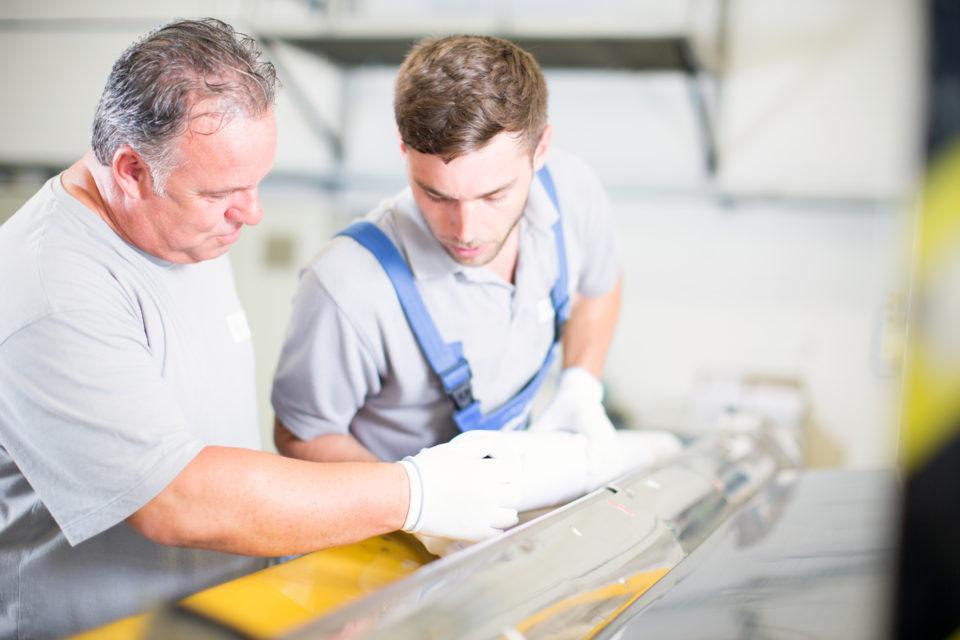 Zwei Mitarbeiter der Produktion an einer Maschine